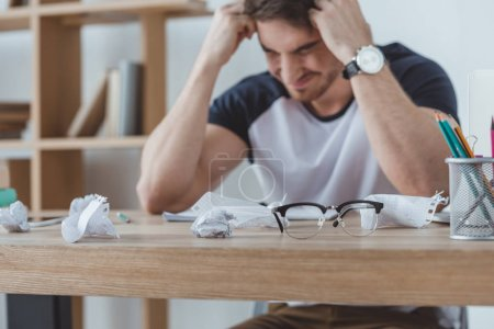 depressed student studying at table with crumpled papers and eyeglasses