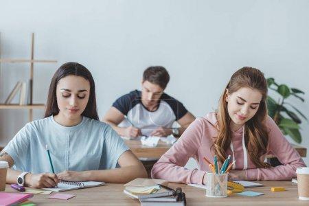 Photo pour Jeunes étudiants assis aux tables et à l'examen d'écriture ensemble - image libre de droit
