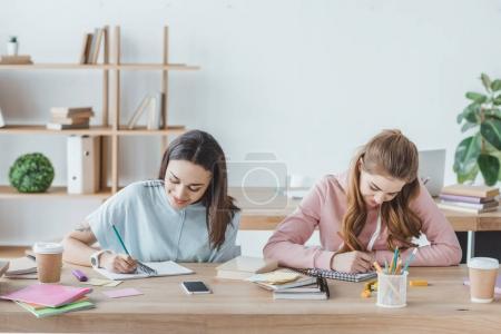 female multiethnic students writing examination together