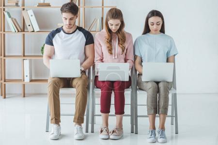 Photo pour Jeunes étudiants assis et étudiant avec des ordinateurs portables ensemble - image libre de droit