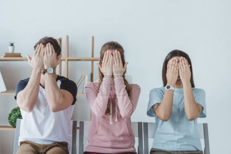 young students closing faces with hands