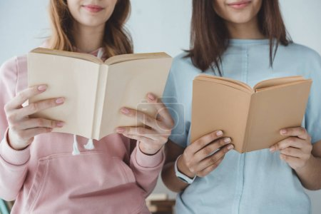 cropped view of female students reading books together