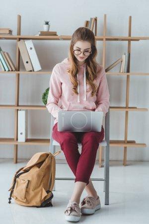 Photo pour Étudiant blonde assis avec sac à dos et en utilisant un ordinateur portable - image libre de droit
