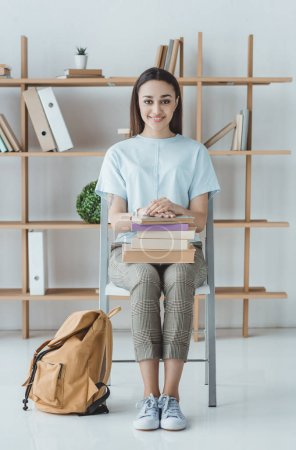 brunette student sitting with books and backpack