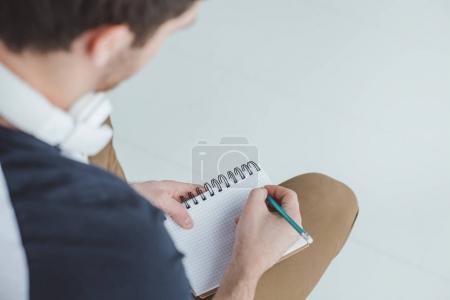 Photo pour Recadrée vue d'étudiant avec un casque écrire dans cahier - image libre de droit