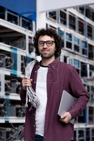 handsome young computer engineer with laptop and wires working at cryptocurrency mining farm