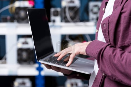 cropped shot of computer engineer working with laptop at cryptocurrency mining farm