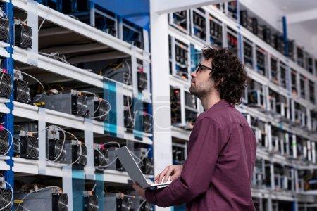 Photo pour Ingénieur informatique travaillant avec ordinateur portable à la ferme minière crypto-monnaie - image libre de droit