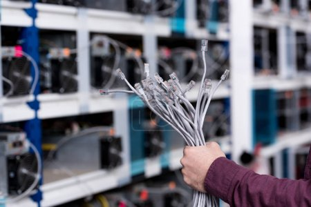 cropped shot of computer engineer holding ethernet wires at cryptocurrency mining farm