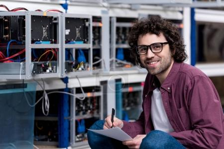 young smiling computer engineer sitting on floor and writing at cryptocurrency mining farm