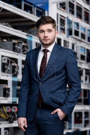 handsome young businessman in stylish suit at cryptocurrency mining farm