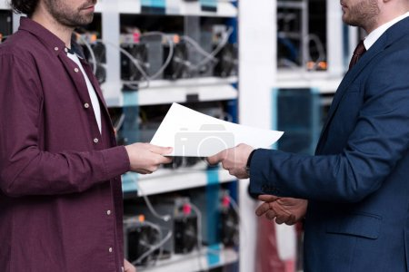 cropped shot of businessman and computer engineer passing documents at cryptocurrency mining farm