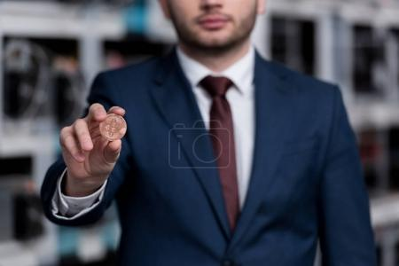 cropped shot of young businessman holding bitcoin at cryptocurrency mining farm
