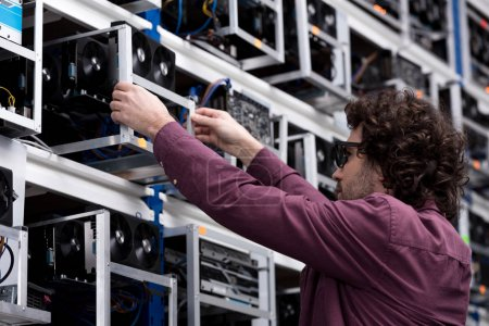 computer engineer taking out box with graphic card at ethereum mining farm