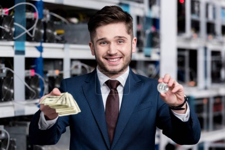 handsome young businessman holding stack of cash and bitcoin at cryptocurrency mining farm
