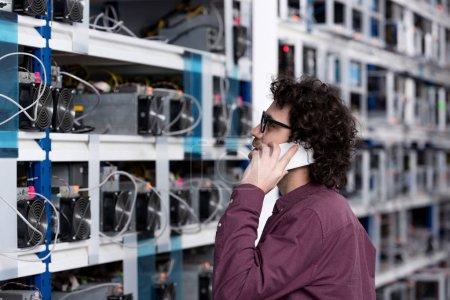 Photo pour Jeune ingénieur informatique parlant par téléphone à la ferme minière éthérique - image libre de droit
