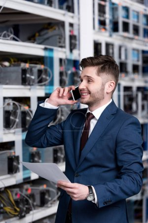 happy young businessman talking by phone at ethereum mining farm