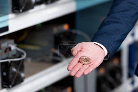 Photo pour Plan recadré de l'homme d'affaires en costume tenant Bitcoin à la ferme minière crypto-monnaie - image libre de droit