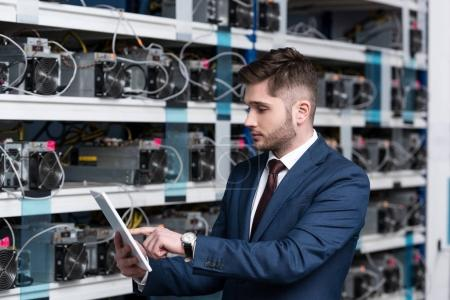 serious young businessman using tablet at ethereum mining farm