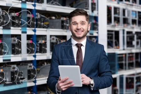smiling young businessman using tablet at ethereum mining farm