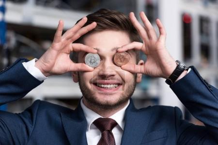 Photo pour Souriant jeune homme d'affaires couvrant les yeux avec Bitcoins à la ferme minière crypto-monnaie - image libre de droit