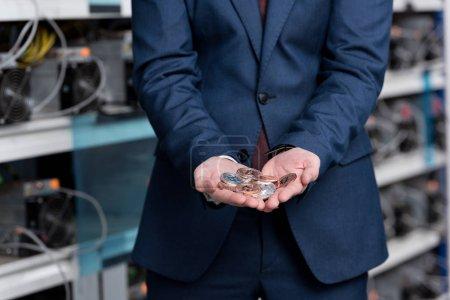 Photo pour Plan recadré d'homme d'affaires avec tas de bitcoins dans les mains à la ferme minière crypto-monnaie - image libre de droit