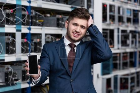 failed young businessman showing smartphone at cryptocurrency mining farm