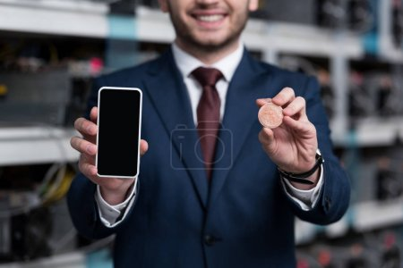 Photo for Cropped shot of businessman showing smartphone and bitcoin at cryptocurrency mining farm - Royalty Free Image