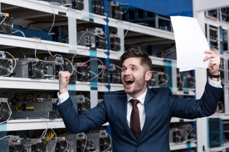 happy young businessman with papers celebrating victory at cryptocurrency mining farm