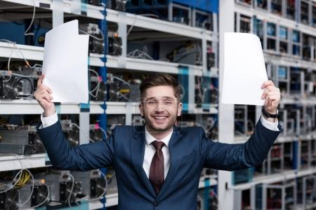 successful young businessman with papers celebrating victory at cryptocurrency mining farm