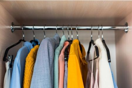 Photo for Colorful female clothes hanging on rack in wardrobe - Royalty Free Image