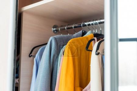 colorful female clothes hanging on rack in cabinet