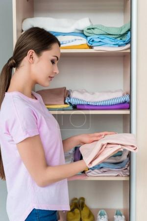 attractive young woman holding folded shirt near cabinet