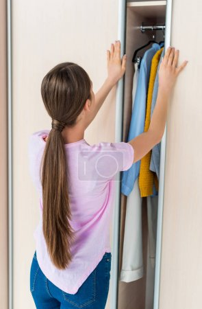 Photo for Rear view of young woman opening cabinet with clothes at home - Royalty Free Image