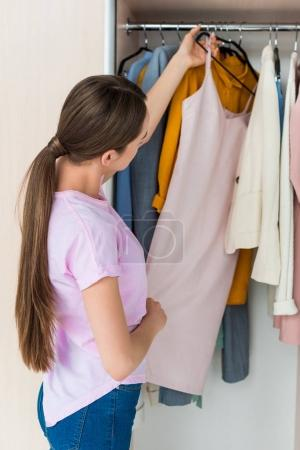 Photo for Attractive young woman choosing clothes from rack - Royalty Free Image