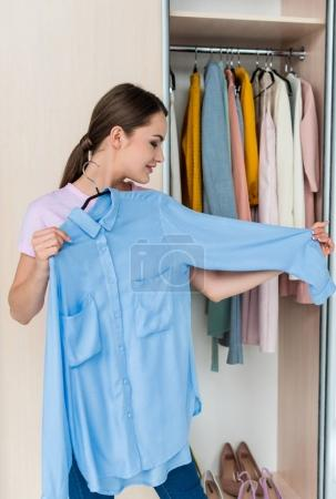 Photo for Smiling young woman looking at shirt on hanger - Royalty Free Image
