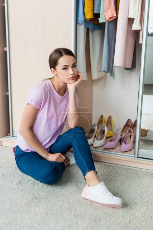 Photo for Thoughtful young woman sitting near cabinet with clothes and shoes at home - Royalty Free Image