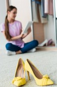 close-up shot of high heels standing on floor with young woman using tablet at home blurred on background