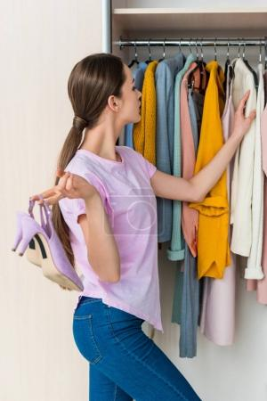 Photo for Attractive young woman holding shoes and choosing clothes from cabinet at home - Royalty Free Image