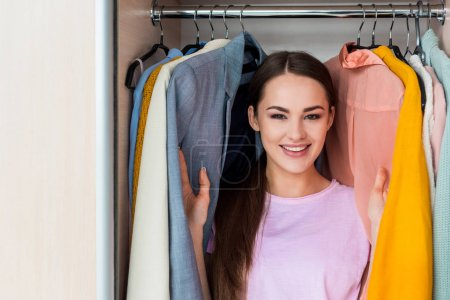 Photo for Happy young woman standing between hanging clothes in cabinet at home - Royalty Free Image