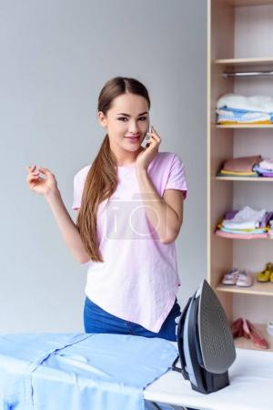 happy young woman ironing clothing and talking by phone at home