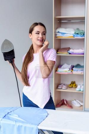 attractive young woman ironing clothing and talking by phone at home