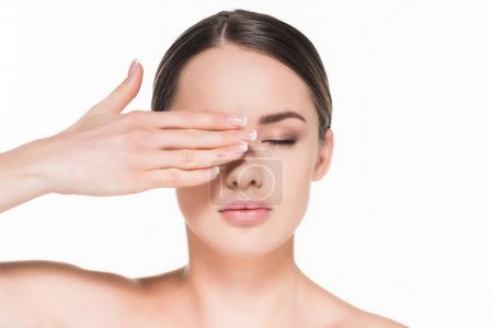 attractive young woman covering eye with one hand isolated on white