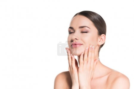 smiling young woman touching her face with eyes shut isolated on white