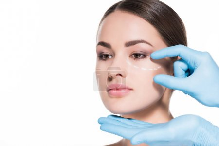 close-up shot of doctor touching face of woman with dotted line for plastic surgery isolated on white
