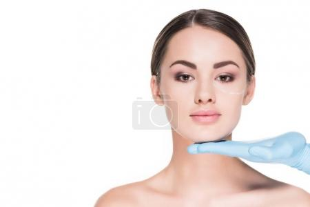 doctor touching face of attractive woman with dotted line for plastic surgery isolated on white