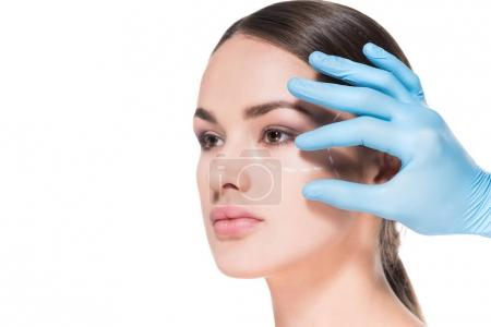 doctor touching face of young woman with dotted line for plastic surgery isolated on white