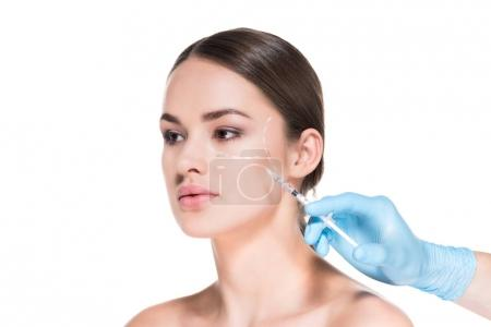 Photo for Cropped shot of doctor making beauty injection for young woman while she looking away isolated on white - Royalty Free Image