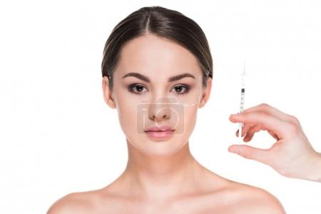 beautiful young woman with dotted line drawn on face for plastic surgery and hand holding syringe isolated on white