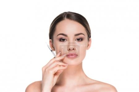 young woman with dotted line drawn on face for plastic surgery holding syringe isolated on white